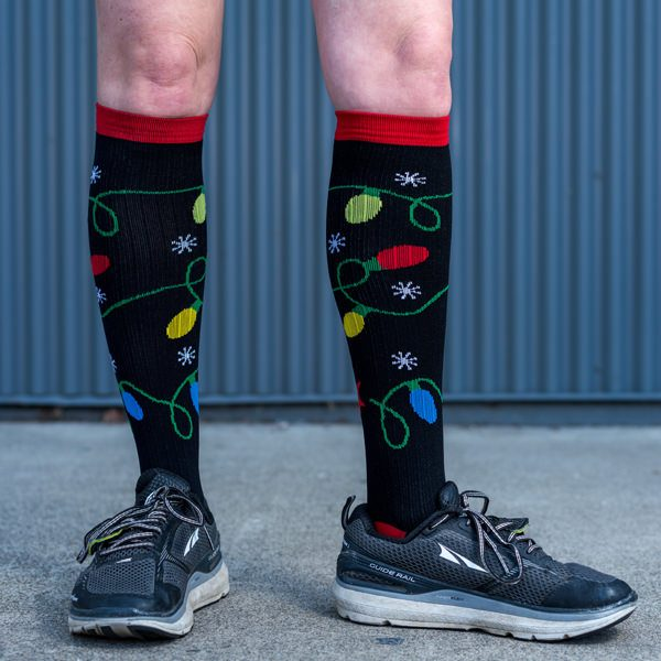 model wearing Christmas light compression socks