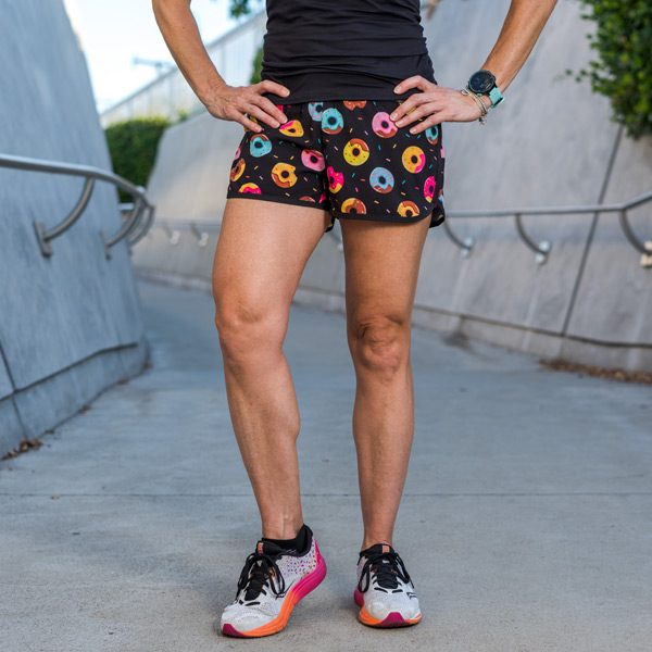 model wearing running shorts with pockets featuring mini donuts