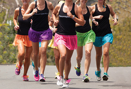 group of women running in sparkle skirts